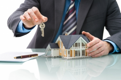 <p>Man holding house presenting keys depicting this section being about buying real estate.</p>